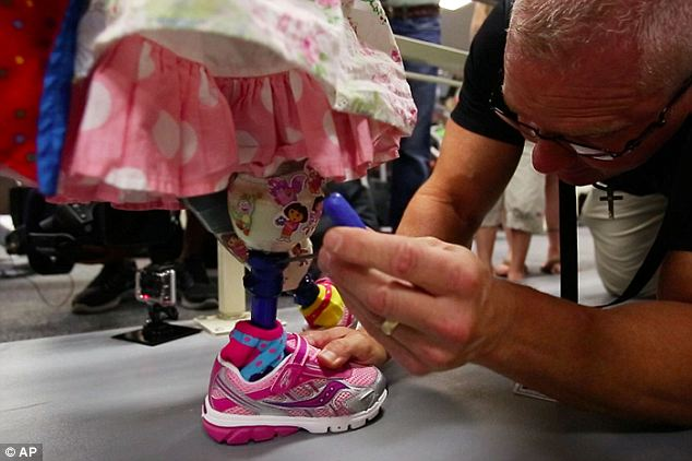 Colorful: Prosthetist Stan Patterson makes an adjustment to one of Ireland Nugent's test legs, accessorized with Dora the Explorer stickers and pink sneakers