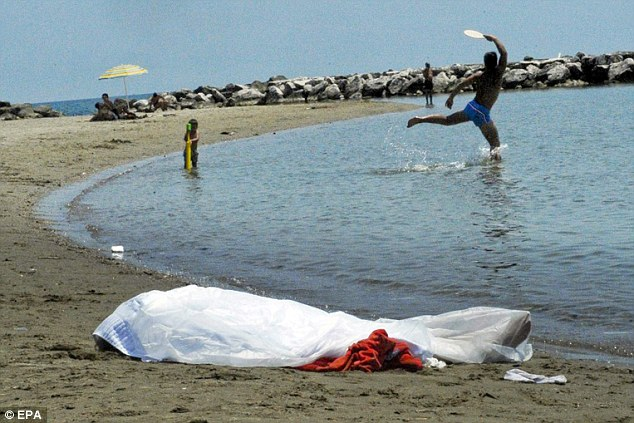 Left on the sand: The body of the woman is ignored as a child paddles and a man plays bat and ball