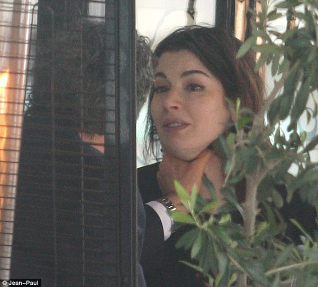 Shock: Charles Saatchi seizes Nigella's throat in the restaurant as she winces with pain during what he called a 'playful tiff'