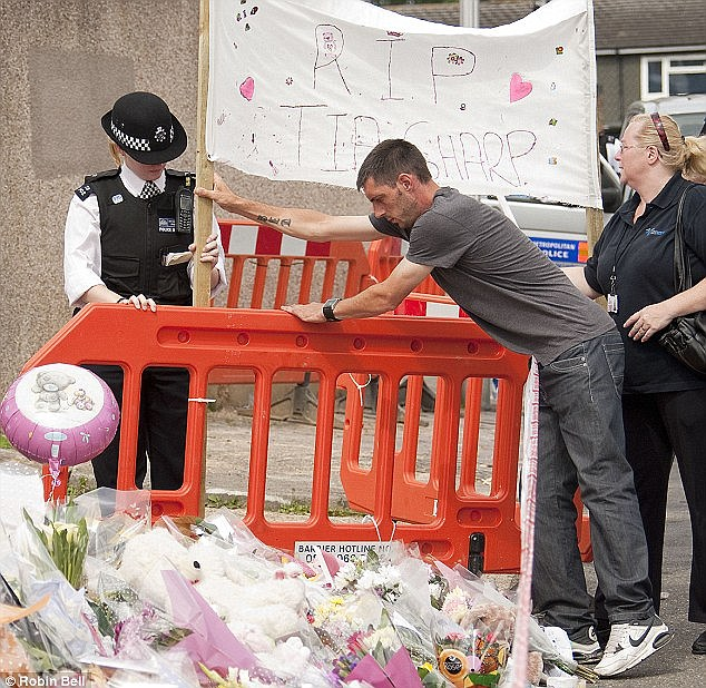 Anguish: Tia's father Steven looks at flowers left for his daughter near her home in south London after she was murdered last summer