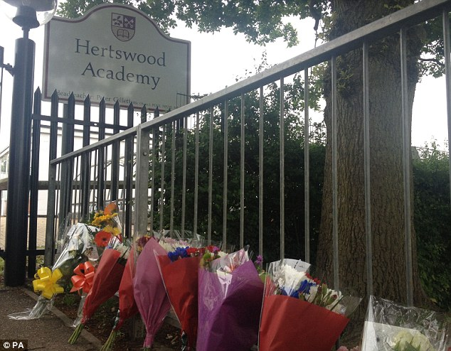 Tribute: Flowers are left outside the gates of Hertswood Academy, in Borehamwood, today after Mert and Charleigh were hit by a train