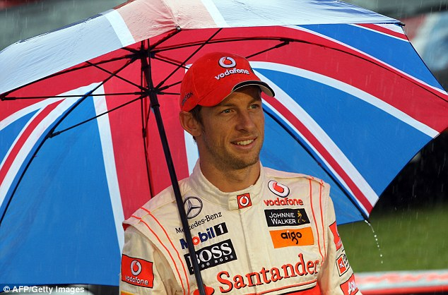 Jenson Button,Formula One driver, stands beneath an umbrella in the rain during a photocall in London