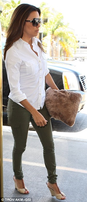 Casual chic: Eva teamed the form-fitting attire with a button up white shirt and a pair of beige and tan wedge shoes
