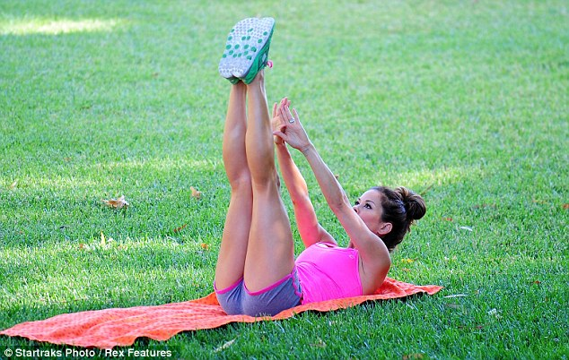 She works out: The mother-of-four showed off her flexibility as she stretched her legs