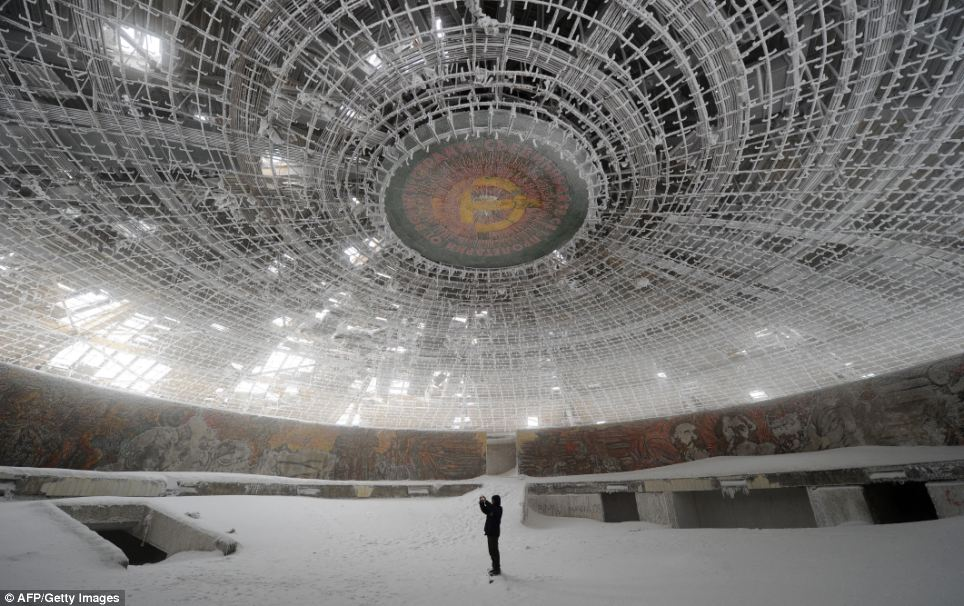 A lone man takes pictures inside the crumbling House of the Bulgarian Communist Party on Mount Buzludzha, no longer needed after the party has lost its grip on the country