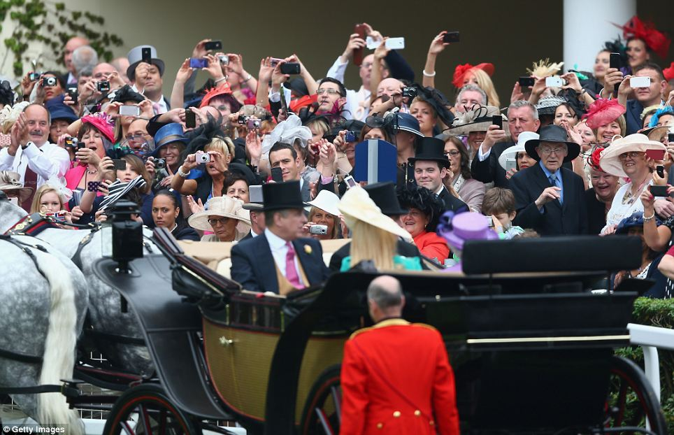 Racegoers take photographs of the Queen, Peter and Autumn Phillips and Prince Andrew, as the Royal carriage procession arrives at the Parade ring outside the grand stand on Ladies' Day during day three of Royal Ascot
