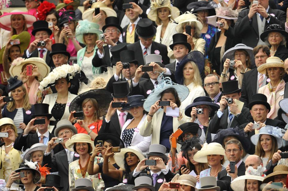 Crowds wield cameras and cameraphones as the Royal procession makes its way past the enclosure on Ladies Day