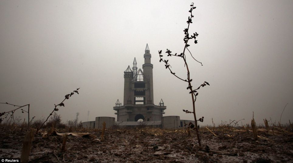 A grim-looking unfinished castle stands uncompleted in a field after funds were withdrawn due to disagreements with the local government and farmers
