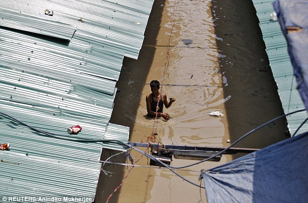 A man wades through a flooded alley at a shopping arcade after heavy monsoon rains caused the rise in waters
