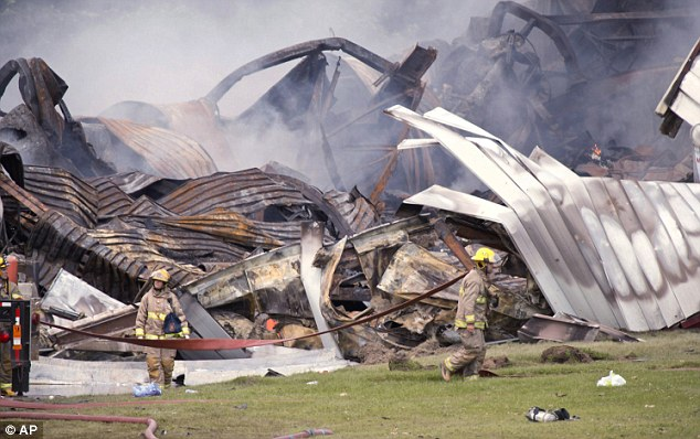 Fire crews: Firefighters clean up following an explosion at the B.E.M. fireworks factory