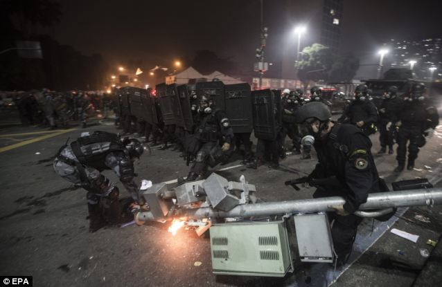 Damage: Brazilian riot policemen remove a vandalized traffic light in order to advance during riots following a demonstration joined by hundreds of thousands in Rio de Janeiro last night