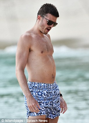Nice shorts: Carrick sports a patterned print on his swimming trunks while relaxing on the sandy beach