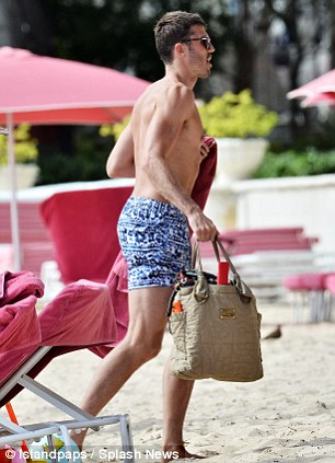 Off I go: Carrick gathers his things before walking off down the beach
