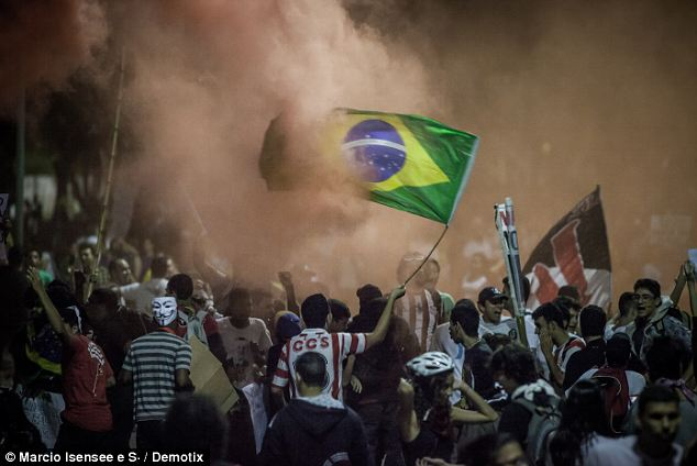 Revolution: A football shirt-clad protester waves the Brazilian flag through clouds of smoke and teargas during violent clashes between protesters and police in Rio de Janeiro last night