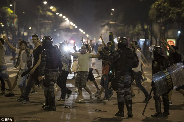 Unarmed: Brazilian protesters walk with raised arms as riot police look during Rio's mass protests last night