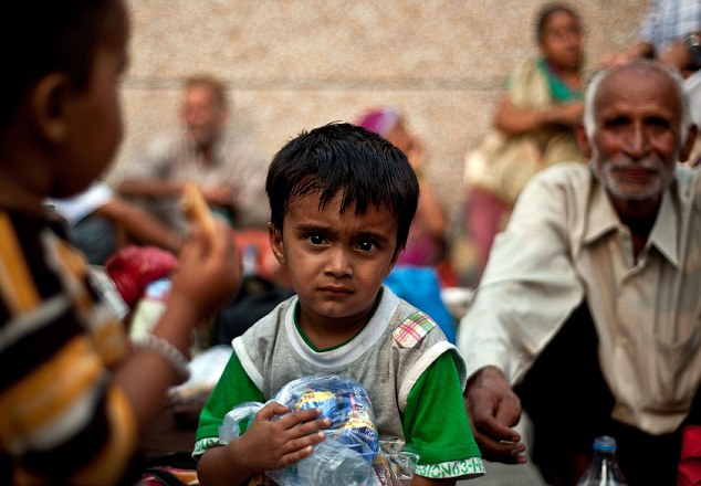 Safe: A boy rescued from flood-hit areas waits with others before being sent to relief camps in Dehradun, state capital of Uttarakhand