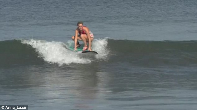One surfer struggles to get to her feet as she reaches the crest of a wave