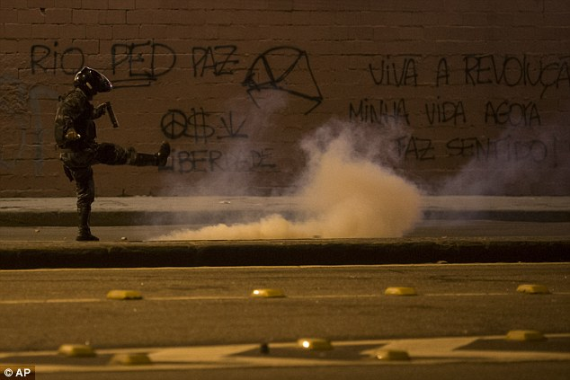 'Noise and truculence': A riot police officer kicks a tear gas canister in Brazil, where the president spoke out on primetime television to say the 'voice of the street' could not be confused with the 'noise and truculence of some troublemakers'