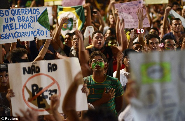 United in protest: Crowds of Brazilians hold up signs in Fortaleza as thousands of demonstrators poured onto the streets across the country