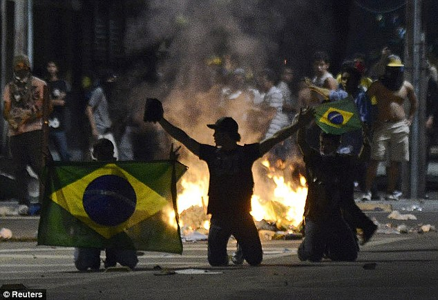 Passion: Demonstrators on their knees wave Brazilian flags in Fortaleza as they voice their anger at the country's government