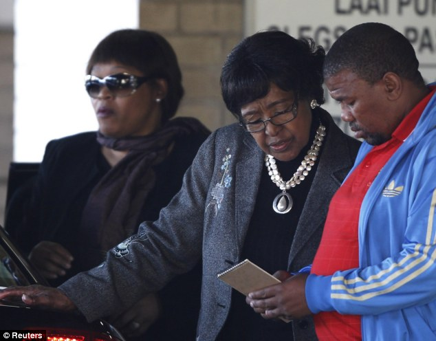 Family worries: Winnie and Zindzi Mandela, ex-wife and daughter of Nelson Mandela, pictured with an unidentified man at the hospital last week, are said to be discussing whether to continue the 94-year-old's treatments