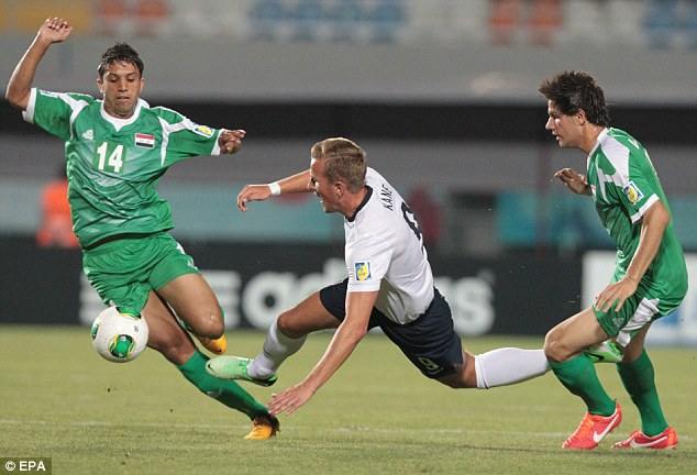 Going down: England's Harry Kane is brought down by the Iraq defence