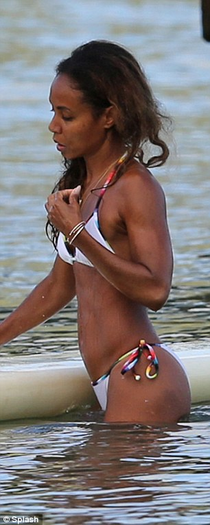 Teeny tiny: The mother-of-two wore a small white bikini with multi-coloured straps for her beach session