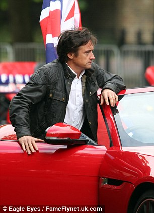 Richard Hammond stands at his red Jaguar