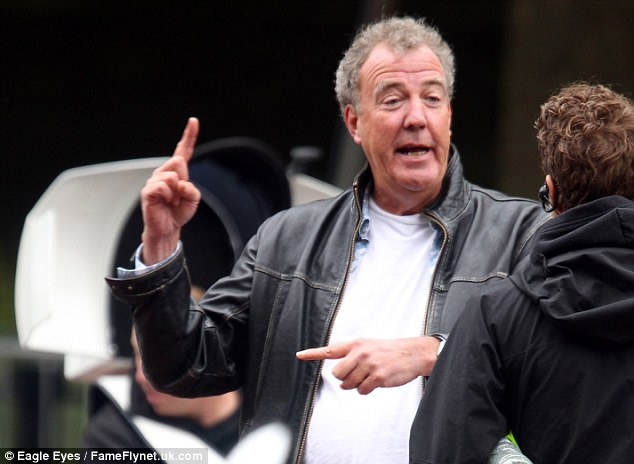Clarkson gestures wildly as he talks to a colleague. The presenter is known for his outlandish opinions