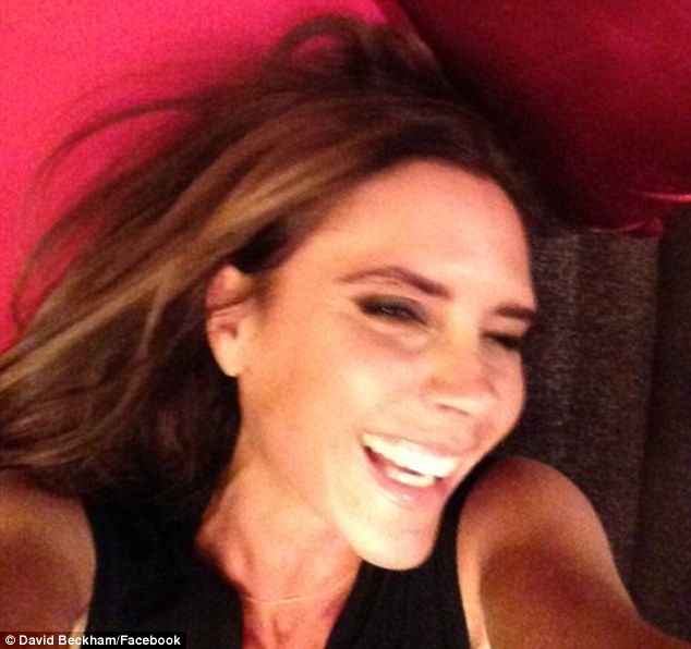 I told you she smiles: David Beckham posted a laughing snapshot of his wife Victoria on his Facebook page on Sunday