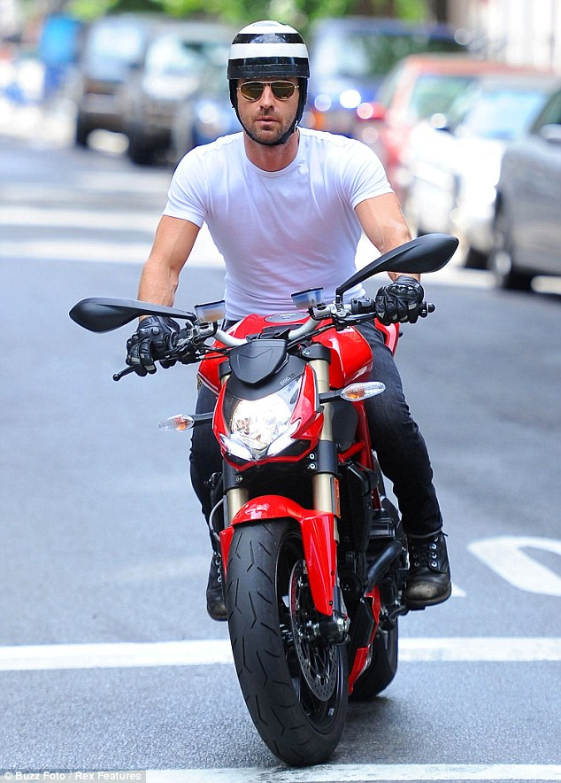 Following the rules: Justin Theroux stopped at an intersection on his red Ducati in NYC on Sunday, showing off his truly fitting biker style