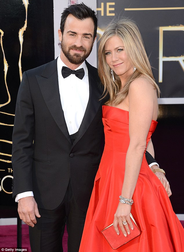 With his bride-to-be: Justin Theroux and Jennifer Aniston, pictured here at the Oscars in February, are said to have potentially stalled their wedding a few months due to hectic work schedules