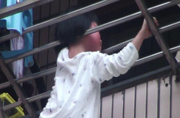 Frantic: Neighbours in Wenzhou, Zhejiang province, dialed 999 while they tried to stop the girl being strangled or breaking her neck