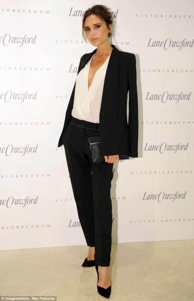 No grey areas: Victoria Beckham looked flawless in a black trouser suit over a low cut white blouse at the launch of her autumn/winter 2013 collection in Beiijing