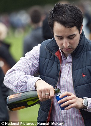 A man pours himself a drink while queuing for Wimbledon