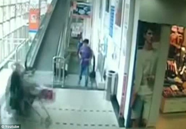 Moment of impact: The overloaded trolley smashes into the shopper, throwing her against a pillar six to seven metres away