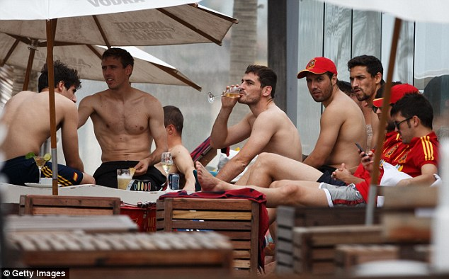Catching rays: Spain's Iker Casillas enjoys a drink amid his teammates, including Santi Cazorla (centre right)