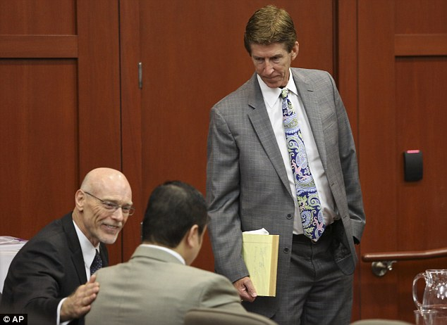 Team: Defense attorney's Don West, left, and Mark O'Mara, right, confer with their client, George Zimmerman as West puts a reassuring hand on his back