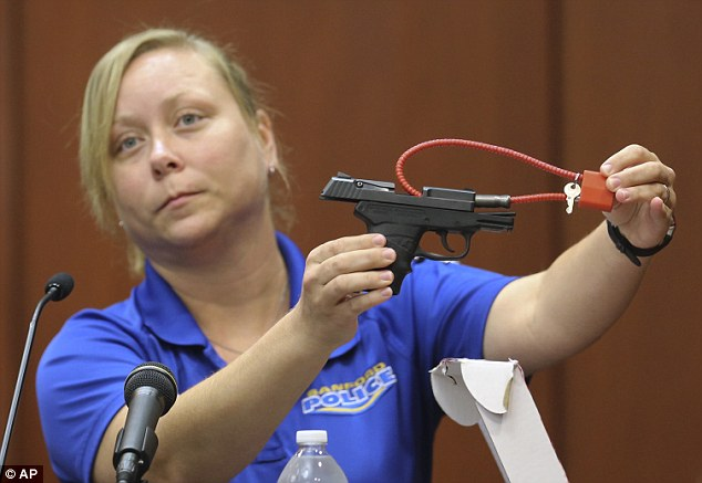 Weapon: Smith shows the jury George Zimmerman's gun, which was collected as evidence at the crime scene, after he used it to shoot Trayvon