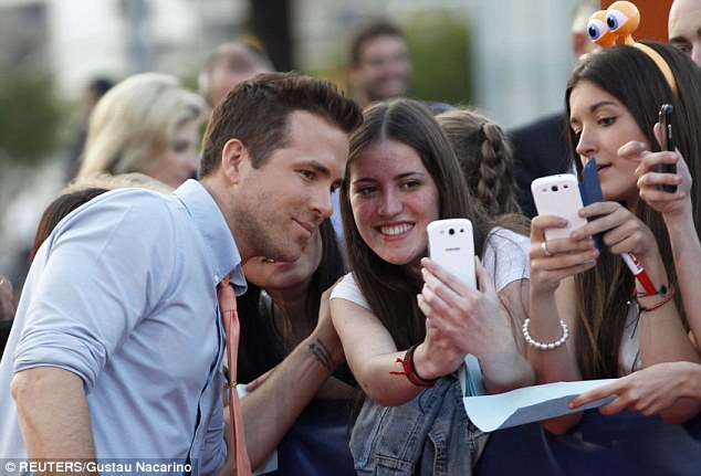 Excited fans: Ryan smiled gingerly for the camera with a female admirer