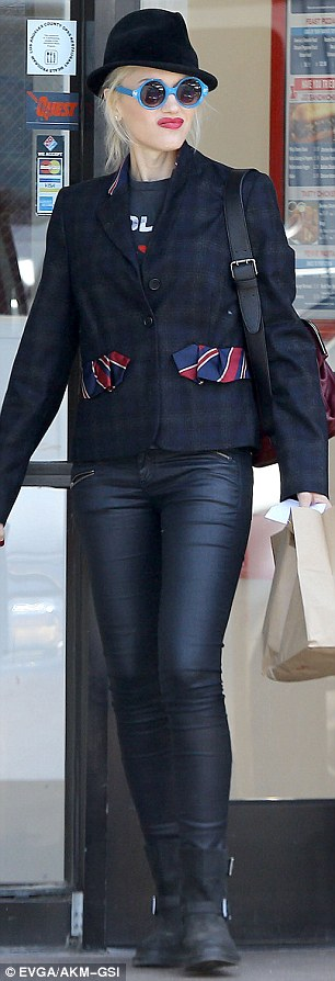 Rocker chic: Gwen donned a pair of tight, black, zip-up trousers, a plaid jacket, and black riding boots