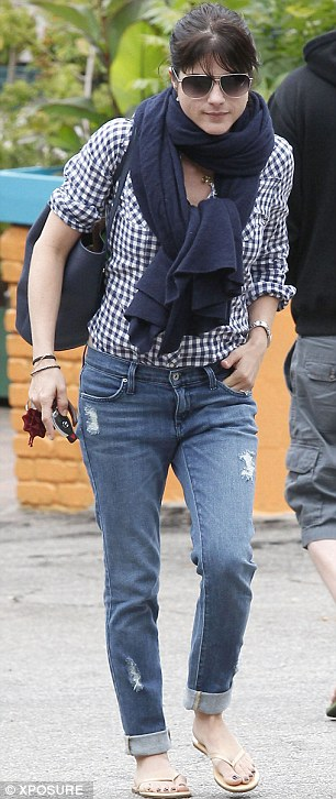 Casual clothing: The 41-year-old wore rolled up and ripped blue jeans with a blue and white checked shirt