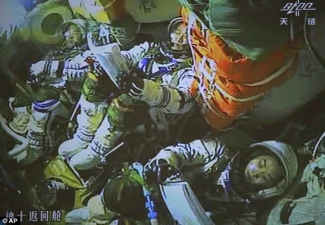 The screen at the Beijing Aerospace Control Center showed the three astronauts in the re-entry capsule prepared for their return.
