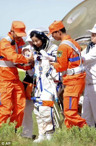 Chinese astronaut Wang Yaping, pictured, is helped out of the re-entry capsule of China's Shenzhou 10 spacecraft after its successful landing on Wednesday.