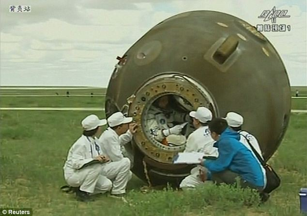 Ground crew talks to astronaut Nie Haisheng before helping him out of the re-entry capsule of China's Shenzhou 10 spacecraft after landing.