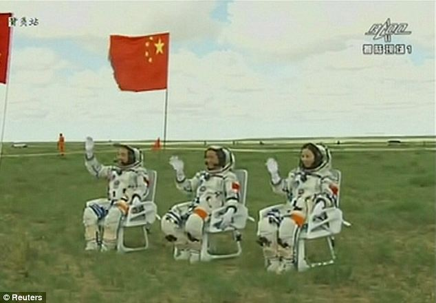 Astronauts (shown left to right) Zhang Xiaoguang, Nie Haisheng and Wang Yaping wave after returning to Earth in the re-entry capsule.