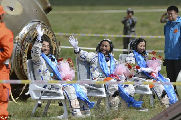 Astronauts Zhang Xiaoguang, Nie Haisheng and Wang Yaping, from left to right, wave after getting out of the re-entry capsule.