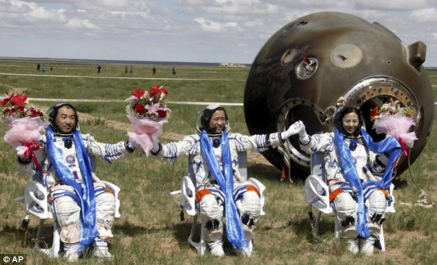 Chinese astronauts Zhang Xiaoguang (left) Nie Haisheng (centre) and Wang Yaping (right) celebrate after getting out of the re-entry capsule of China's Shenzhou 10 spacecraft, pictured.