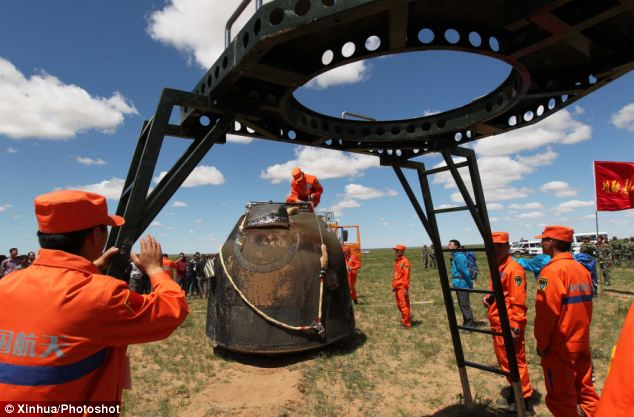 Working staff handle the re-entry capsule of China's Shenzhou-10 spacecraft.
