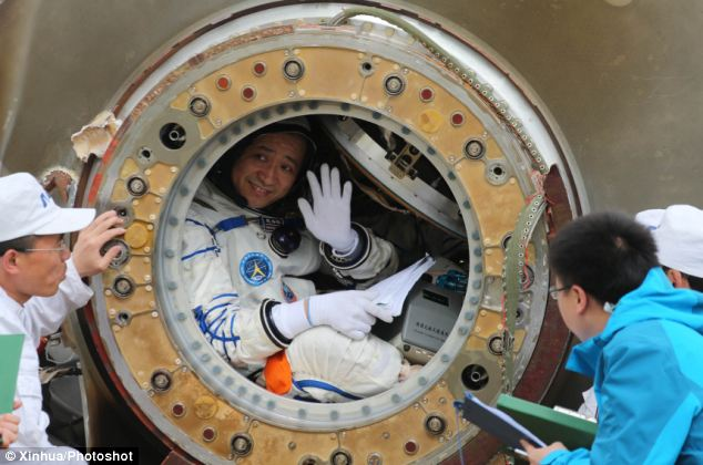 Chinese astronaut Nie Haisheng waves to TV crews and workers from China's manned space program before climbing out of the re-entry capsule of China's Shenzhou-10 spacecraft